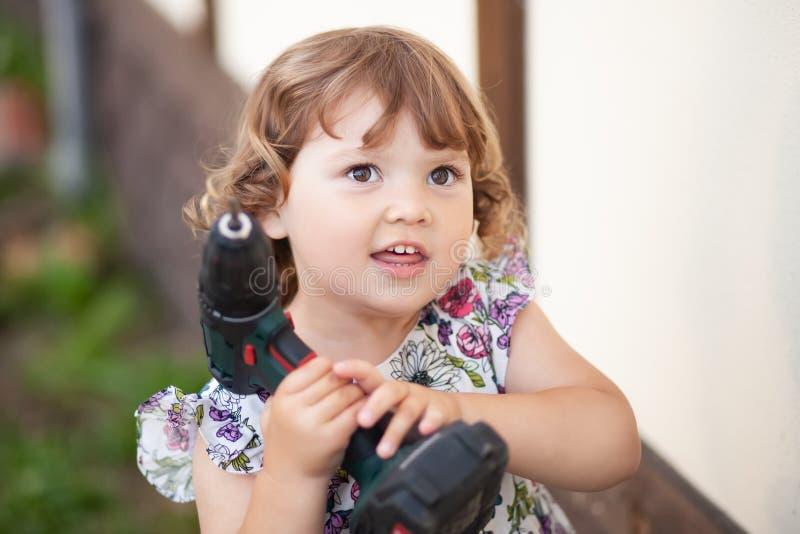 Gullig liten flicka med faders drillborr, utomhus royaltyfri foto