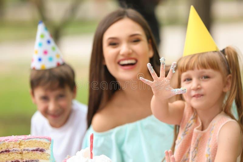 Gullig liten flicka med familjen på födelsedagpartiet utomhus arkivfoto