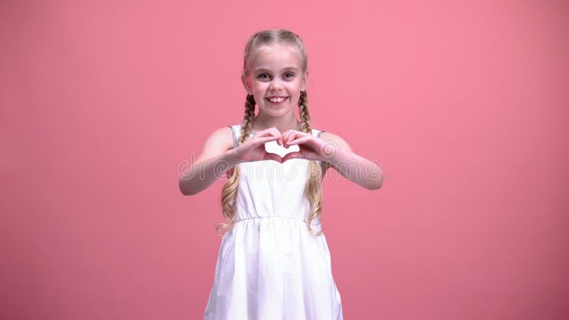 Gullig liten flicka med flätade trådar som visar hjärtagesten, välgörenhet, barnadoption fotografering för bildbyråer