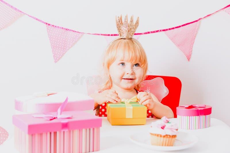 Gullig liten flicka med gåvor på födelsedagpartiet arkivbilder