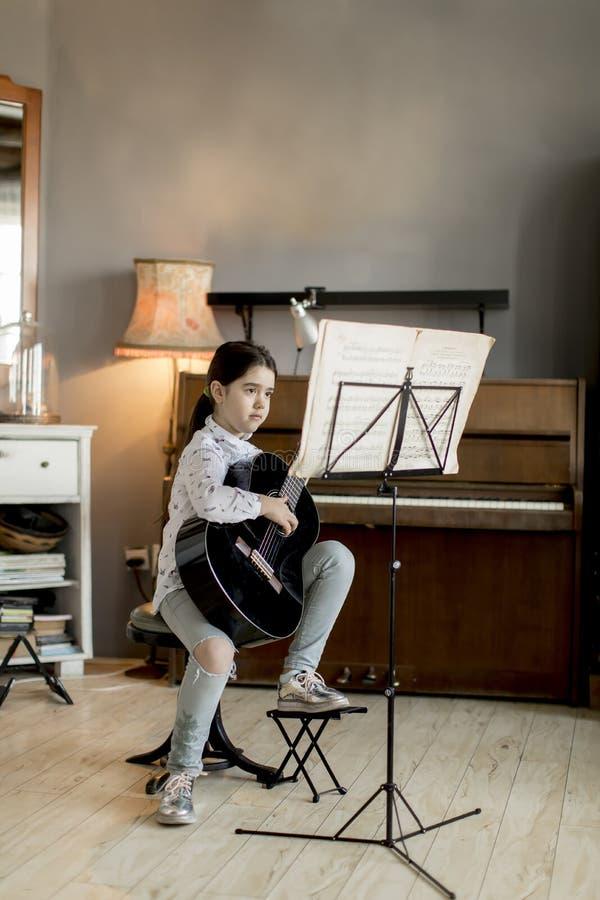Gullig liten flicka med gitarren i rummet fotografering för bildbyråer