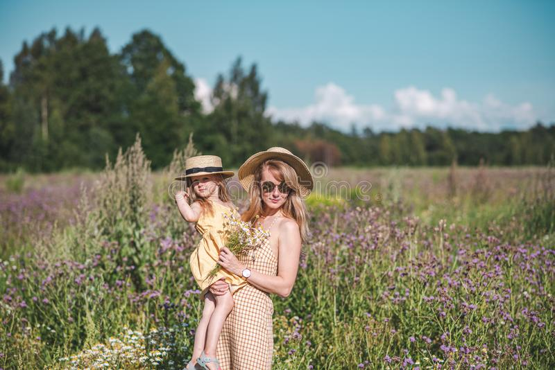 Gullig liten flicka med hennes moder som går i blommafältet arkivbild