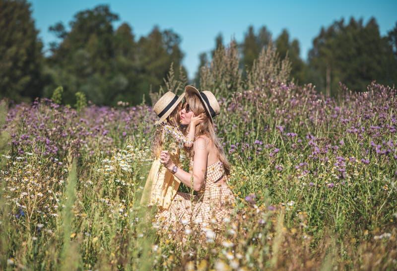 Gullig liten flicka med hennes moder som går i blommafältet royaltyfri foto