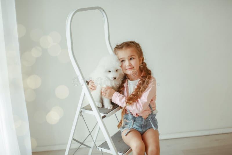 Gullig liten flicka med hunden hemma royaltyfria foton