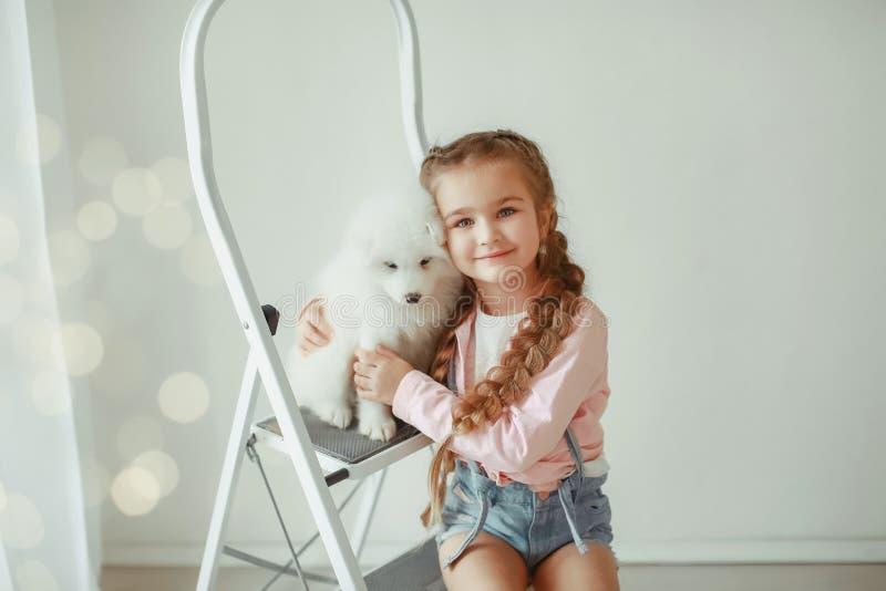 Gullig liten flicka med hunden hemma arkivfoto