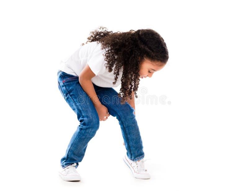 Gullig liten flicka med krullning och mörk hud som är nedböjda till fasta skor royaltyfria foton