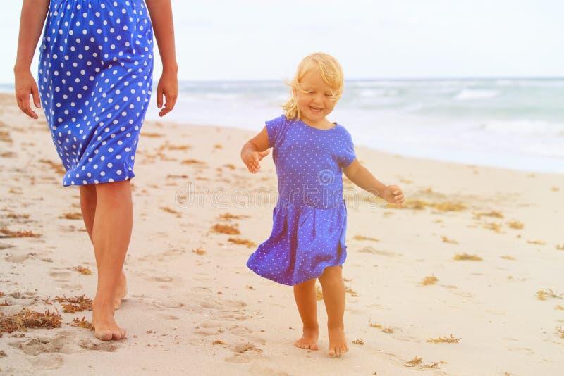 Gullig liten flicka med modern som går på sommarstranden royaltyfri foto