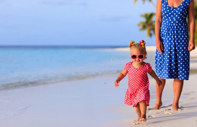 Gullig liten flicka med moderspring på stranden royaltyfri fotografi