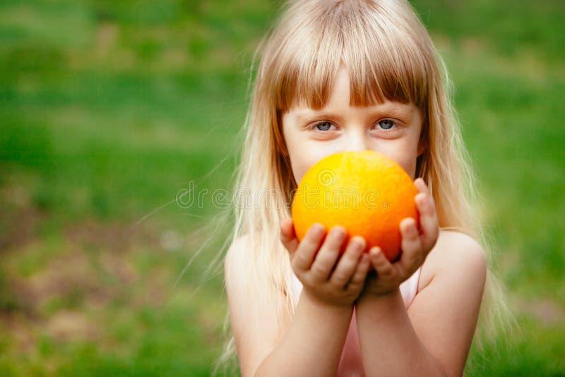 Gullig liten flicka med orange frukt i händer, sunt matbegrepp royaltyfri bild