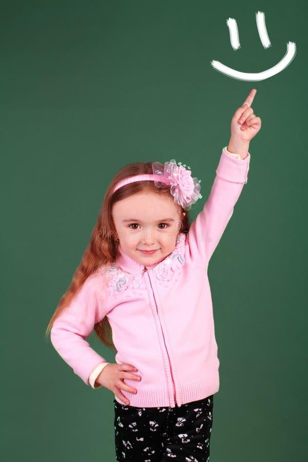 Gullig liten flicka med pekfingret upp royaltyfri foto