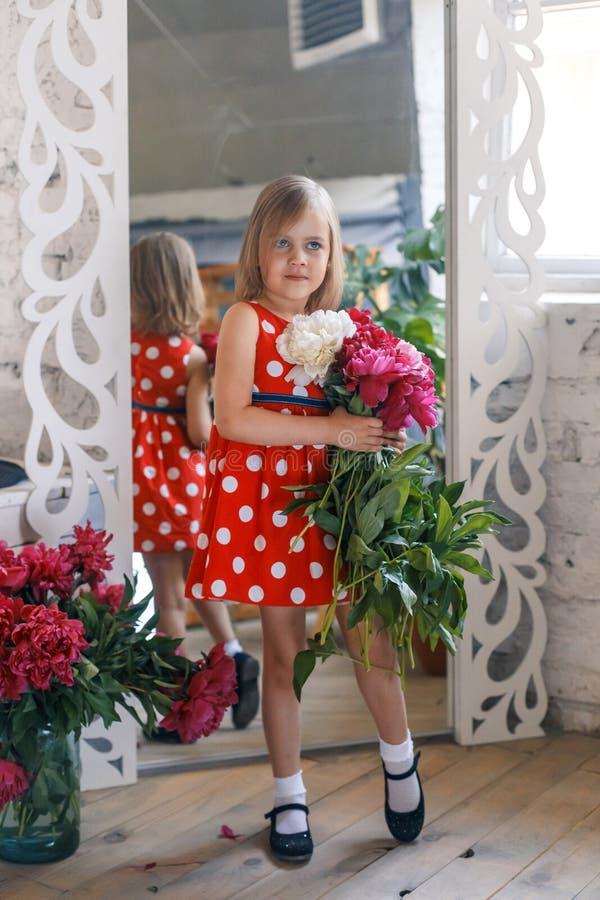 Gullig liten flicka med pioner i studio framme av spegeln arkivfoto