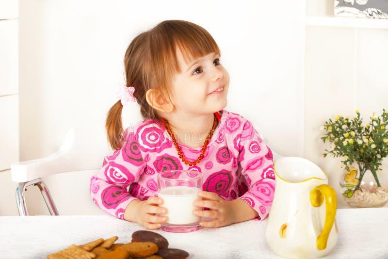 Gullig liten flicka med råttsvansar som sitter och ler fotografering för bildbyråer