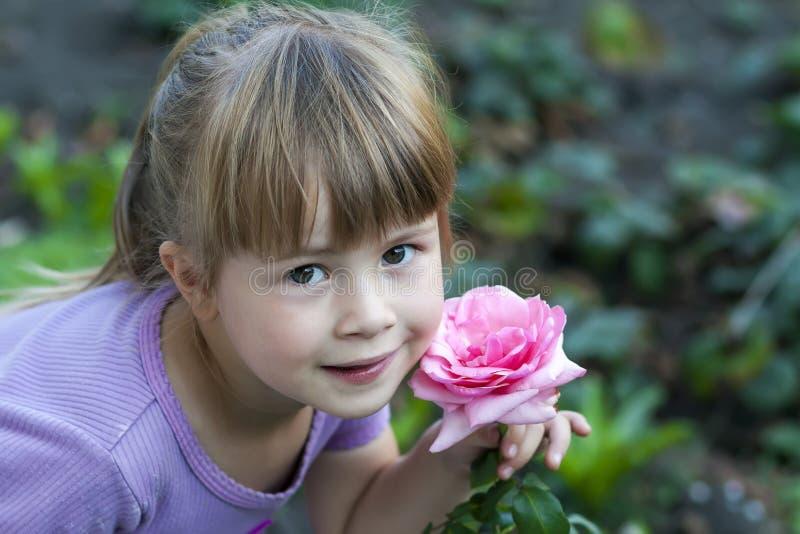 Gullig liten flicka med rosa färgrosblomman arkivfoton