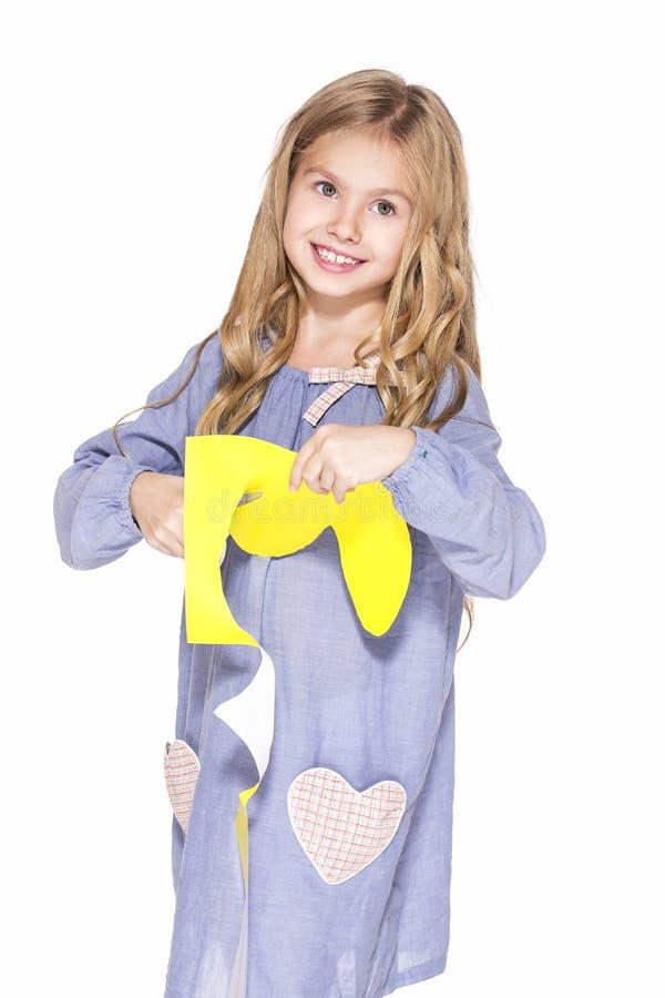 Gullig liten flicka med sax och gulingpapper arkivfoton