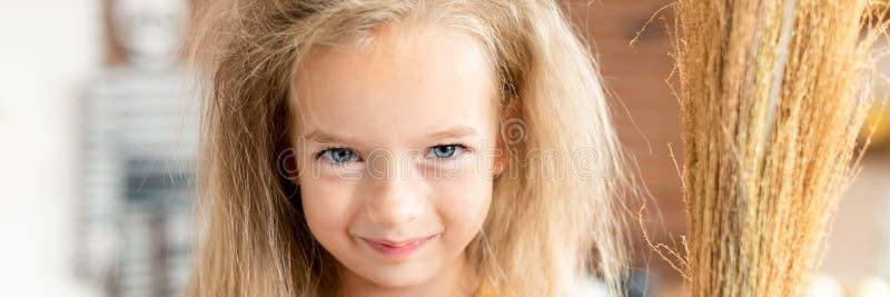 Gullig liten flicka med smutsigt hår, uppklädd som en häxa och att rymma en kvast som ser att le för kamera Allhelgonaaftonparti  royaltyfria foton