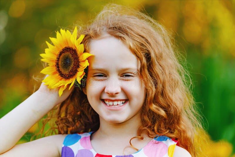 Gullig liten flicka med solrosor i hennes lockiga rödhårig man arkivfoto