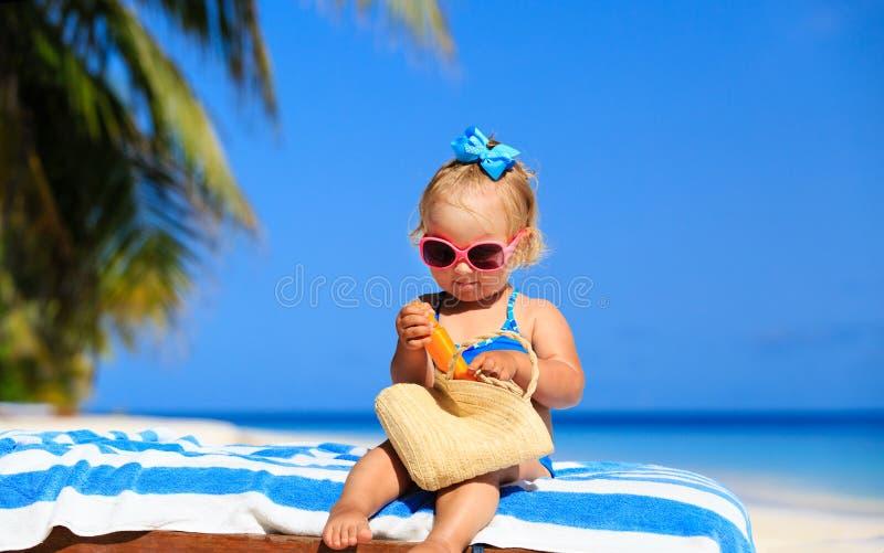 Gullig liten flicka med sunblockkräm på stranden royaltyfri foto
