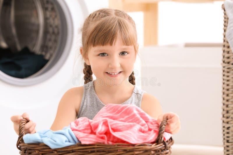 Gullig liten flicka med tvättkorgen arkivbild