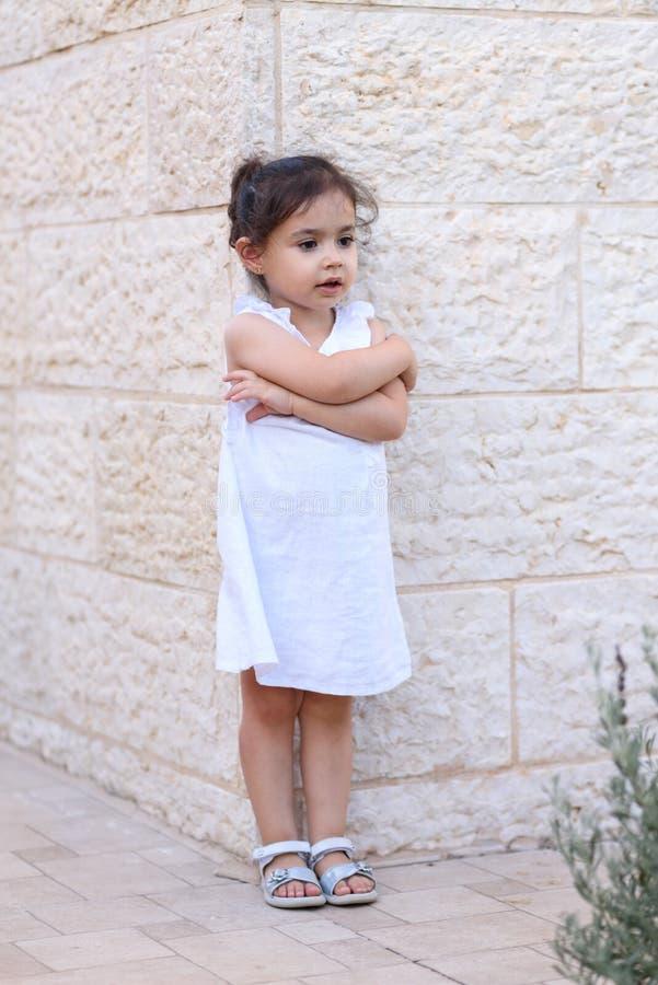 Gullig liten flicka med vitt posera för klänning som är utomhus- field treen arkivfoto