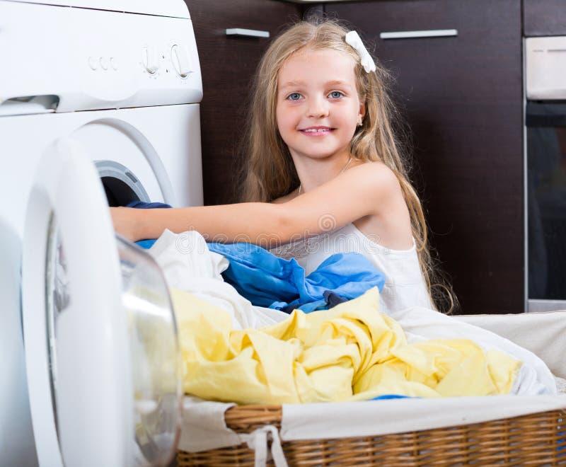 Gullig liten flicka nära tvagningmaskinen royaltyfri fotografi