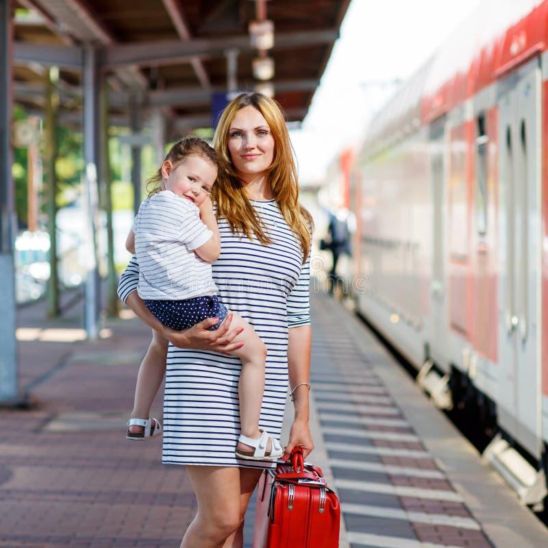 Gullig liten flicka och moder på en järnvägsstation arkivbild