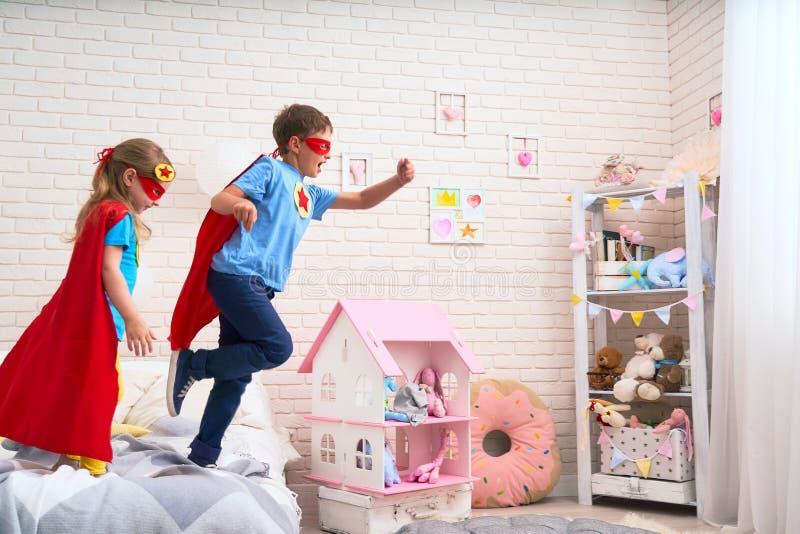 Gullig liten flicka och pojke som hoppar från säng för att flyga, leksuperhero med kappan och maskering hemma i ungesovrum royaltyfria bilder