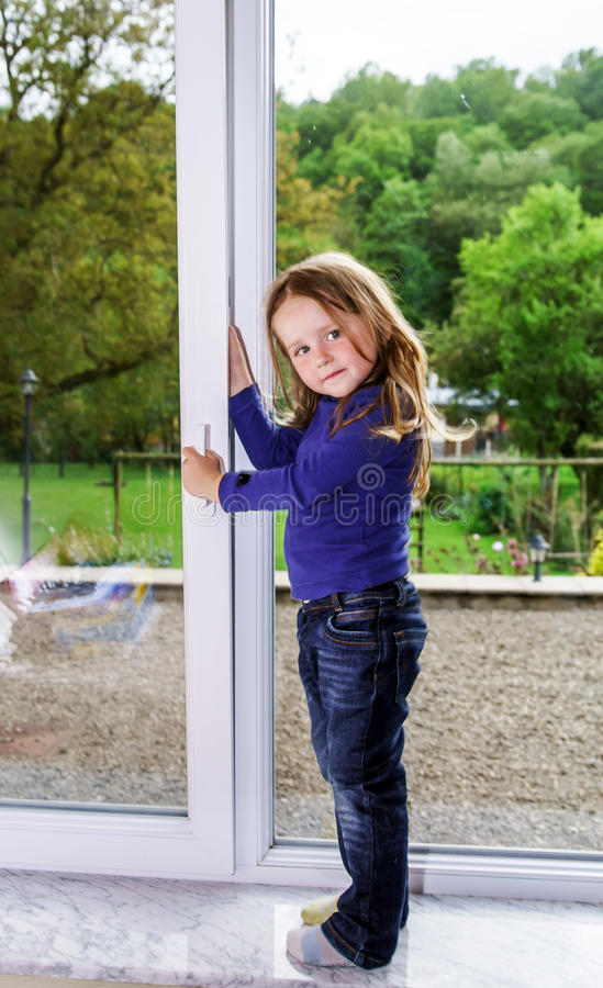Gullig liten flicka och pvc-fönster royaltyfri bild