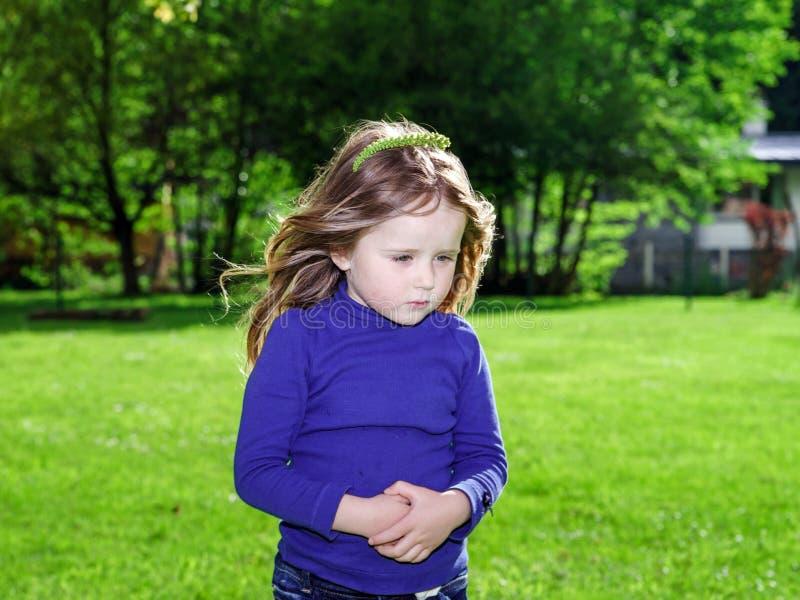 Gullig liten flicka på bakgrund för grönt gräs arkivbilder