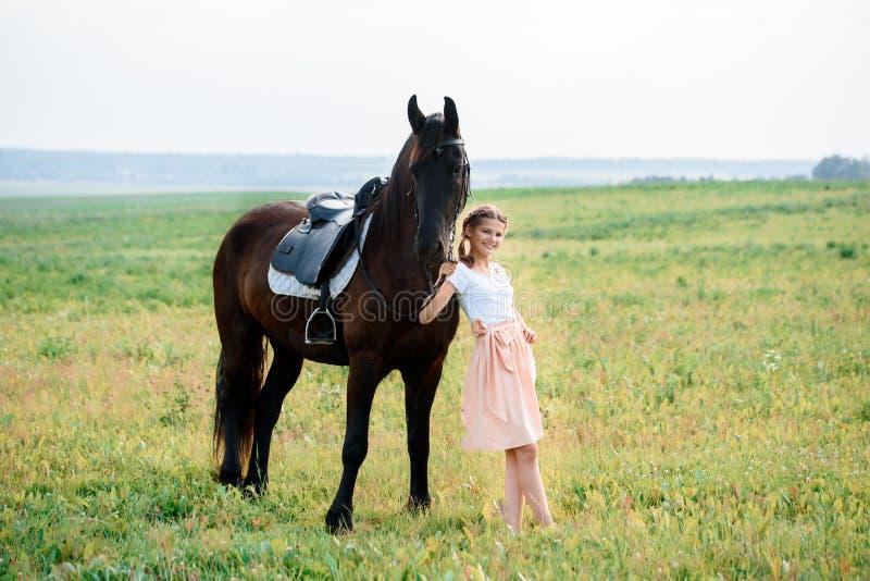 Gullig liten flicka på en häst i en sommarfältklänning solig dag royaltyfria bilder