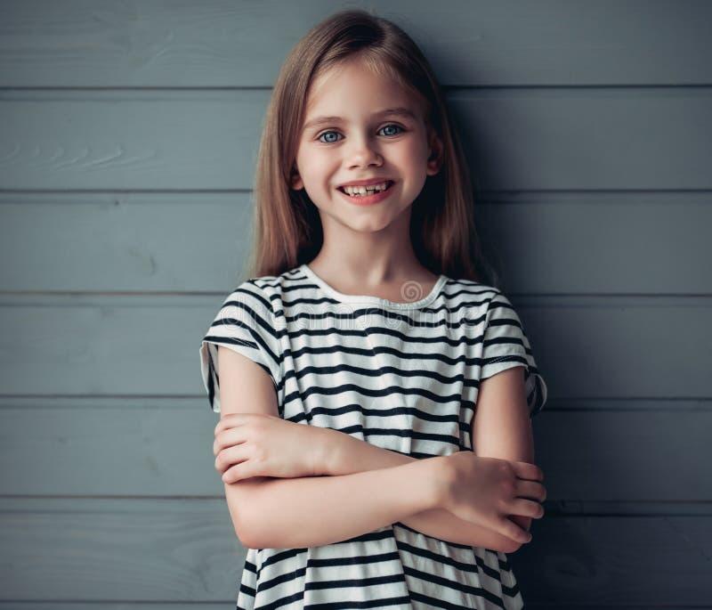 Gullig liten flicka på grå bakgrund arkivbild