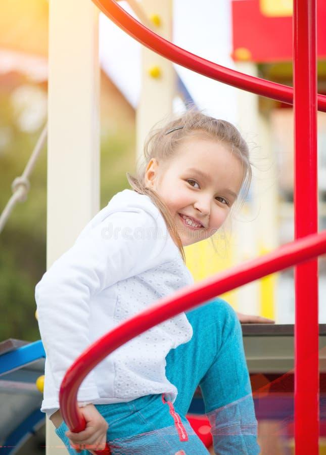 Gullig liten flicka på lekplatsen Utomhus- stående av fem år gammal flicka som ser kameran arkivfoton