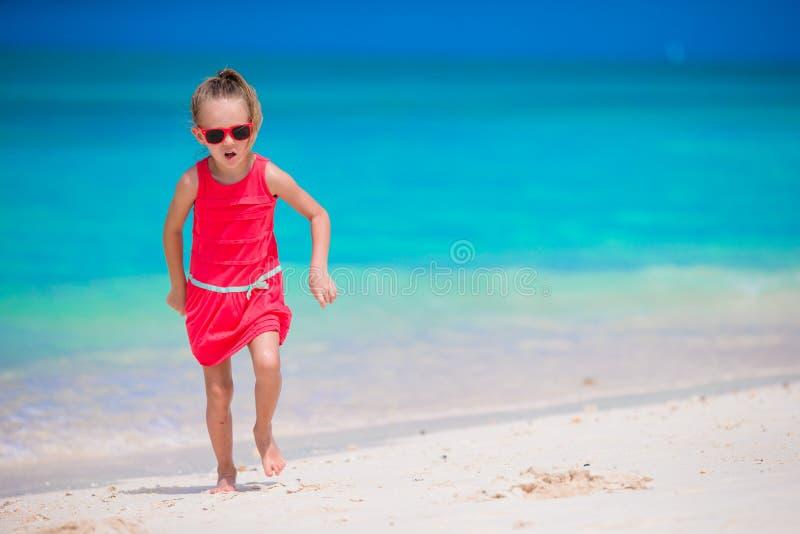 Gullig liten flicka på stranden under tropisk semester royaltyfri fotografi