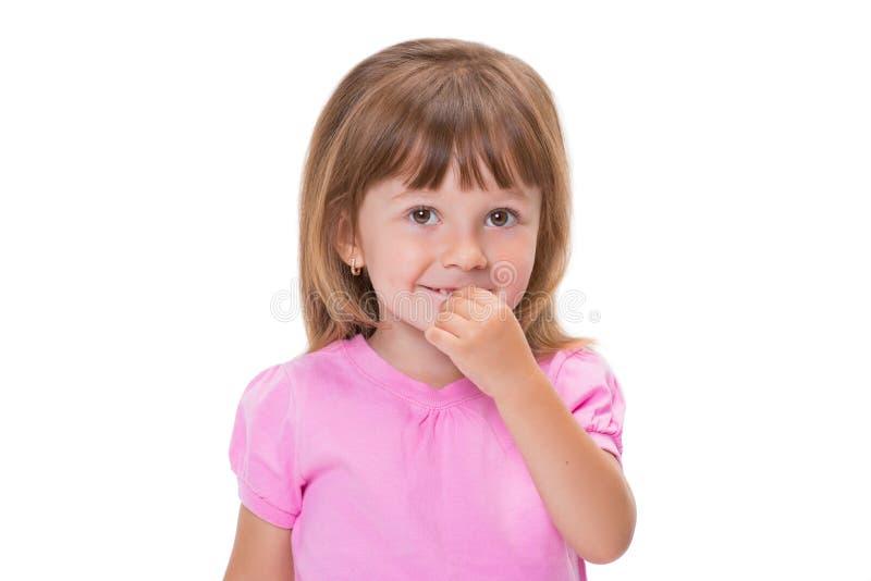 Gullig liten flicka 3 som är årig i rosa t-skjorta, rymmer fingrar i mun, eller tuggor spikar isolerat på vit bakgrund Dålig barn fotografering för bildbyråer