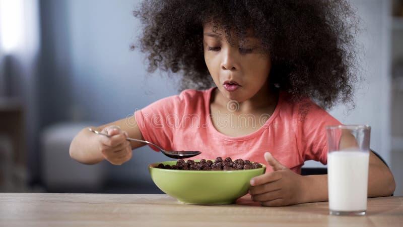 Gullig liten flicka som äter chokladcornflakes för frukosten, risk av sockersjuka royaltyfria foton