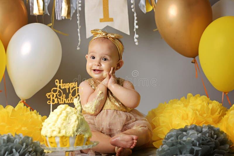 Gullig liten flicka som äter hennes första födelsedagkaka arkivfoton