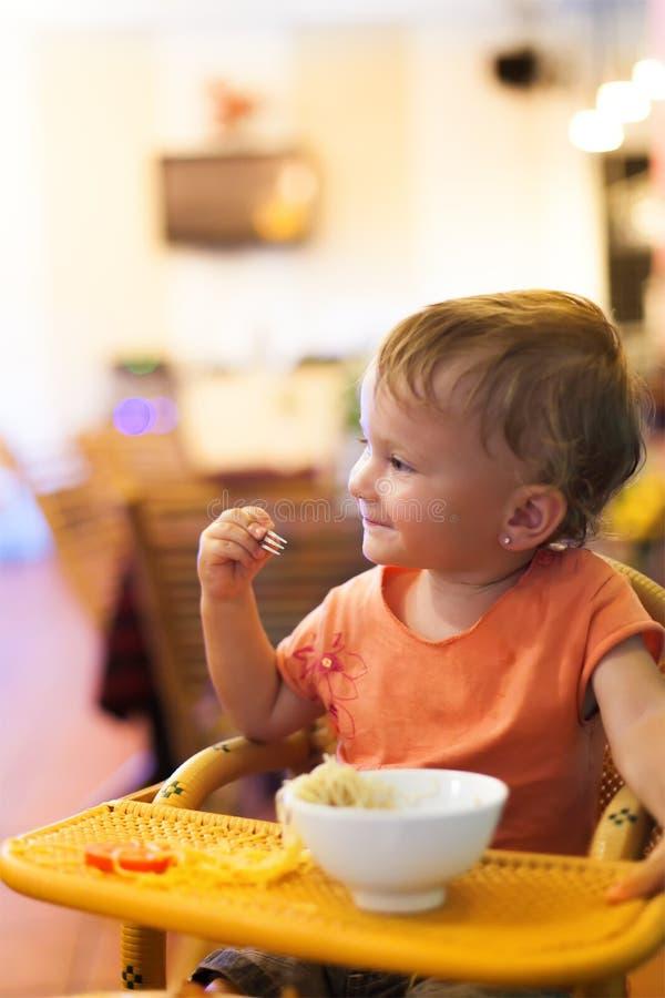Gullig liten flicka som äter spagetti på den lilla restaurangen arkivfoton