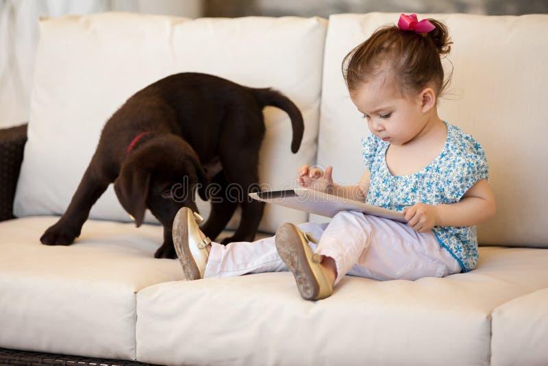 Gullig liten flicka som använder en minnestavla royaltyfri foto