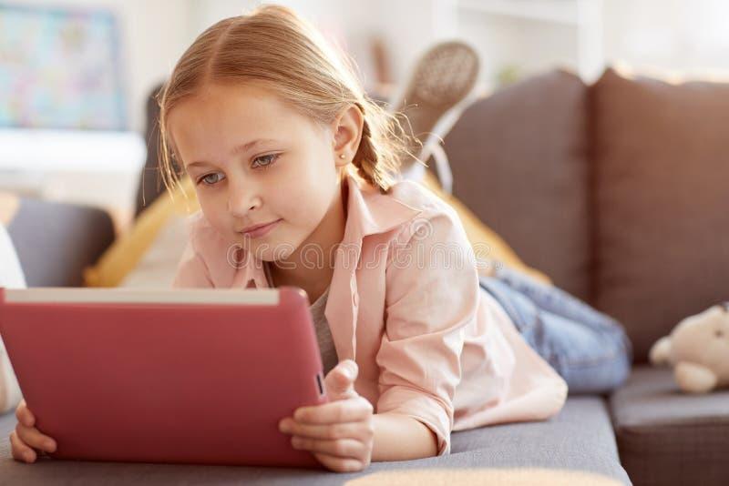Gullig liten flicka som använder minnestavlan fotografering för bildbyråer
