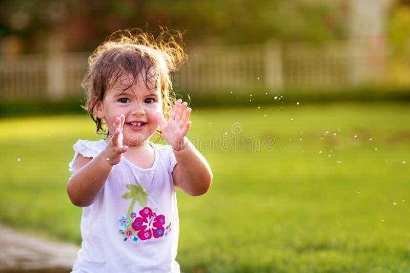 Gullig liten flicka som applåderar henne händer arkivbilder