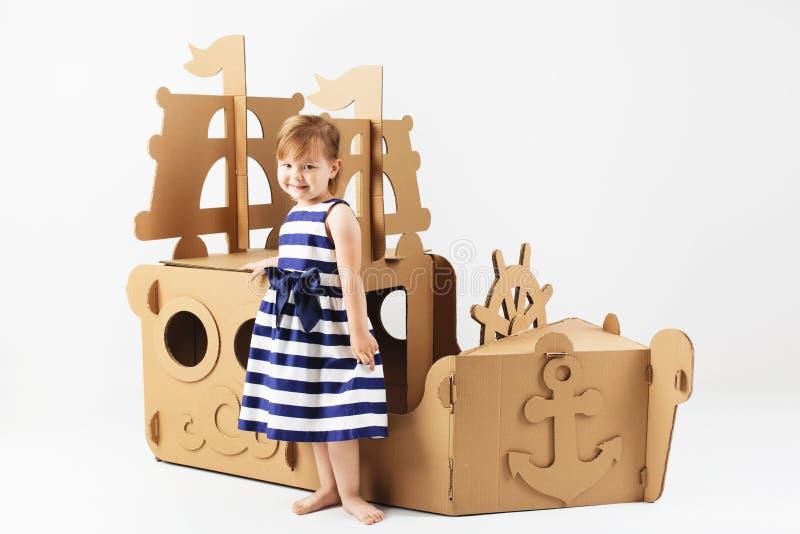 Gullig liten flicka som bär den gjorde randig klänningen i en marin- stilplayin arkivfoto