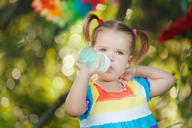 Gullig liten flicka som bär färgrikt klänningdricksvatten fotografering för bildbyråer