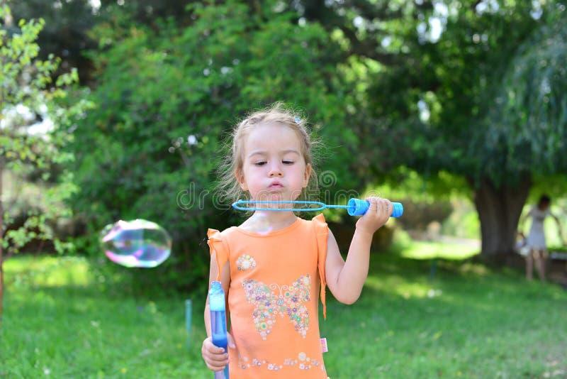 Gullig liten flicka som blåser såpbubblor i natur royaltyfri bild