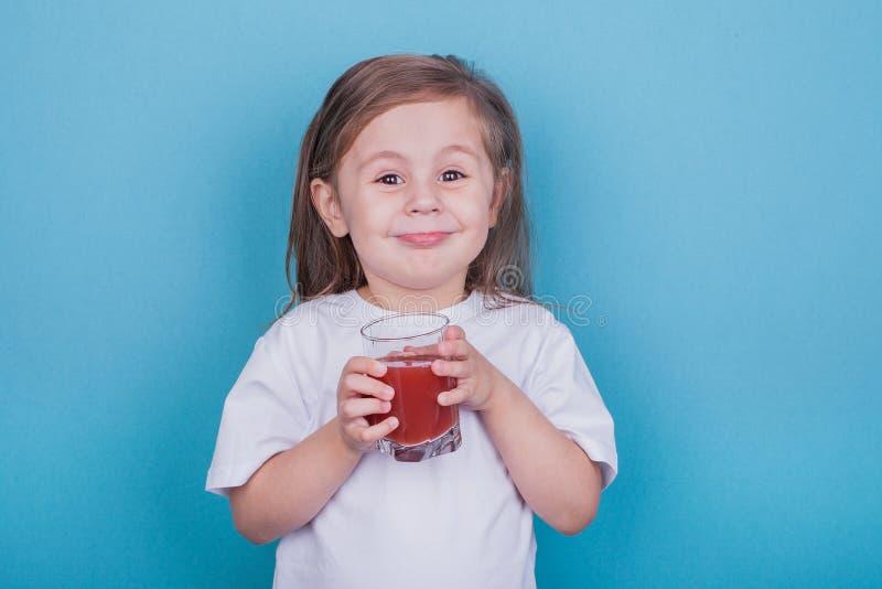 Gullig liten flicka som dricker fruktsaft fr?n exponeringsglas royaltyfria bilder