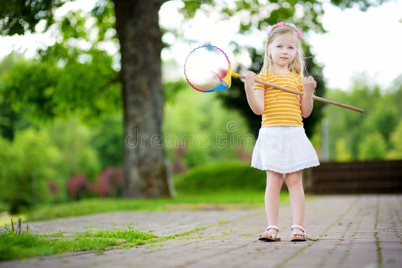 Gullig liten flicka som fångar fjärilar med ettnetto fotografering för bildbyråer