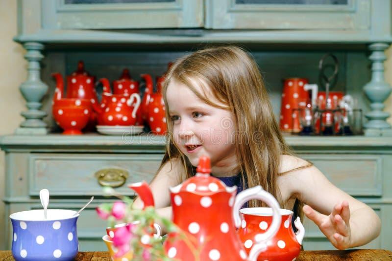 Gullig liten flicka som förbereder te i tekanna royaltyfri fotografi