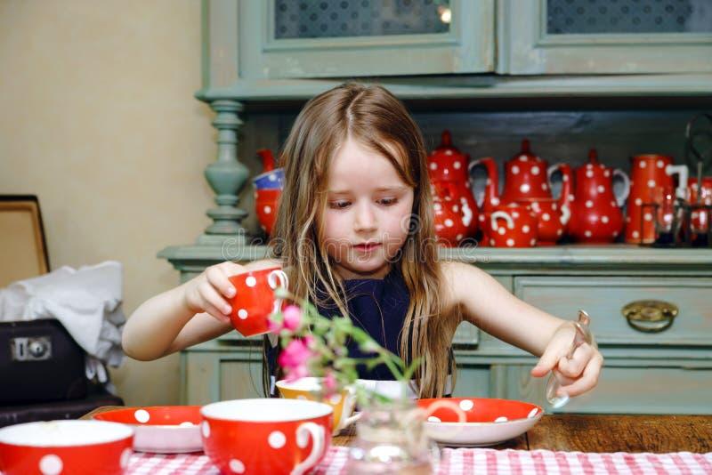 Gullig liten flicka som förbereder te i tekanna arkivbild