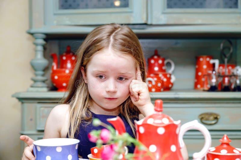 Gullig liten flicka som förbereder te i tekanna arkivfoton