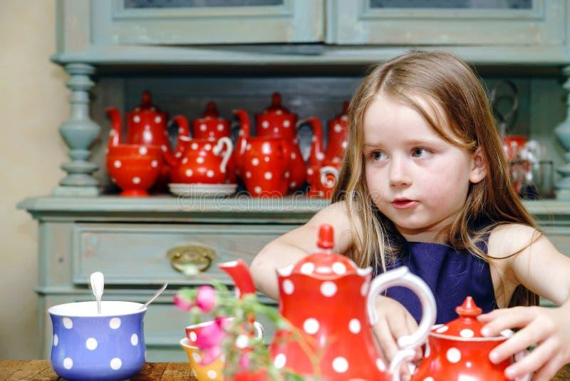 Gullig liten flicka som förbereder te i tekanna fotografering för bildbyråer