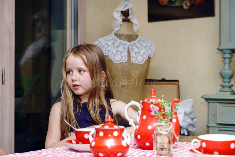 Gullig liten flicka som förbereder te i tekanna arkivfoto