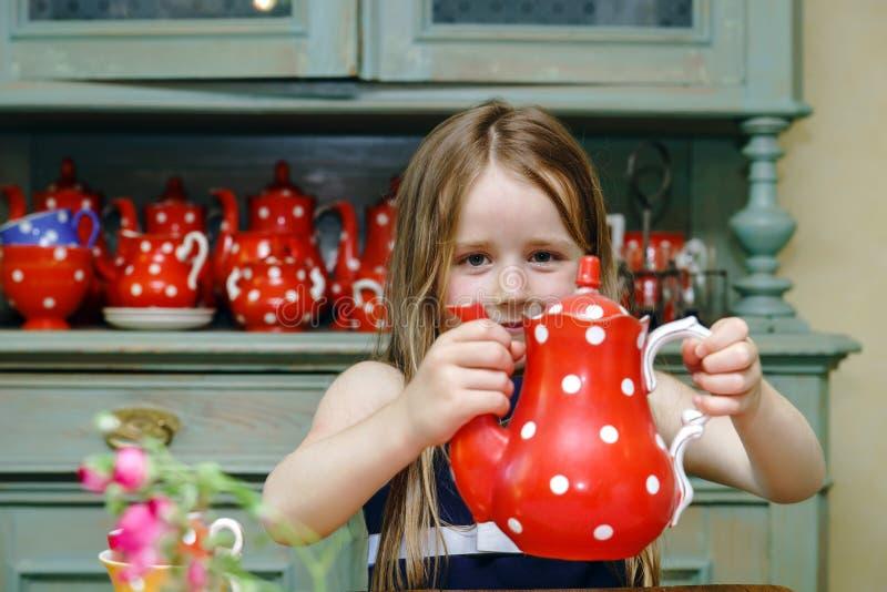 Gullig liten flicka som förbereder te i tekanna arkivbilder